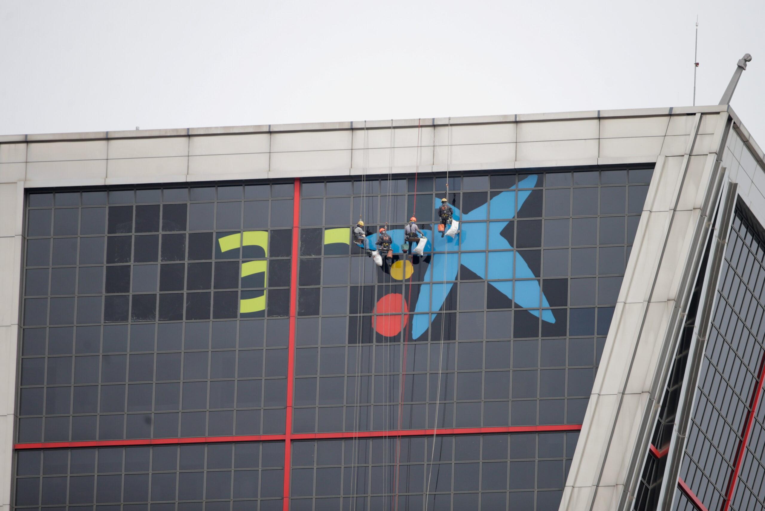 Operaris retiren el logo de Bankia de la seu de l'entitat a Madrid i hi col·loquen el de CaixaBank | ACN - Reuters